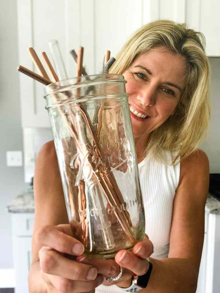 holding the best reusable straws in a glass jar