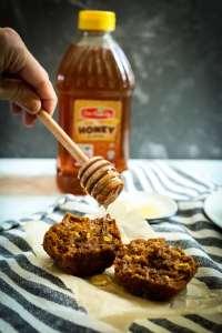 Gluten-Free Pumpkin Muffins Recipe drizzling honey on the muffin