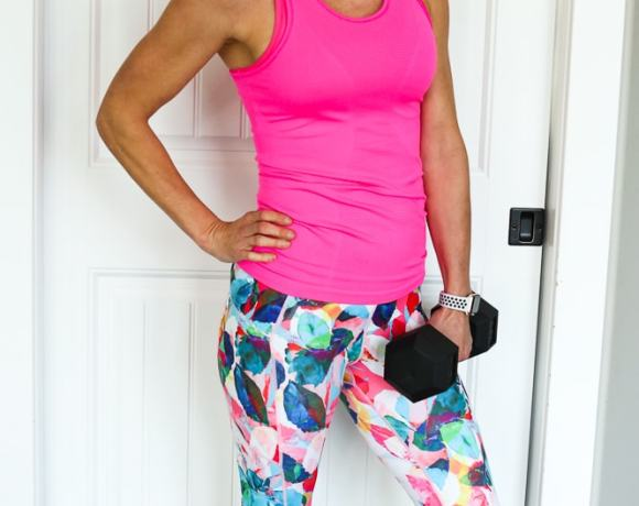 woman in hot pink tank top and floral leggings holding a dumbbell in one arm