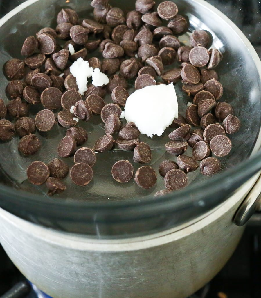 a pan with a glass bowl over it and chocolate chips and coconut oil in the glass bowl