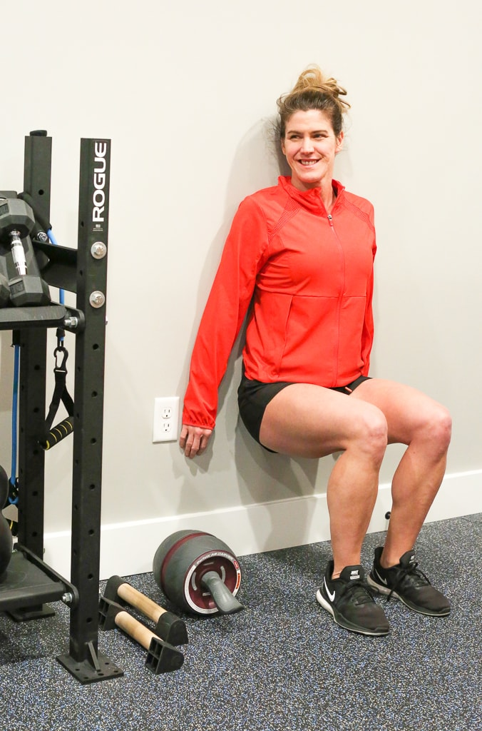 Maryea Flaherty with her back against the wall and legs at a 90 degree angle, performing wall sit exercise in a red jacket and black shorts
