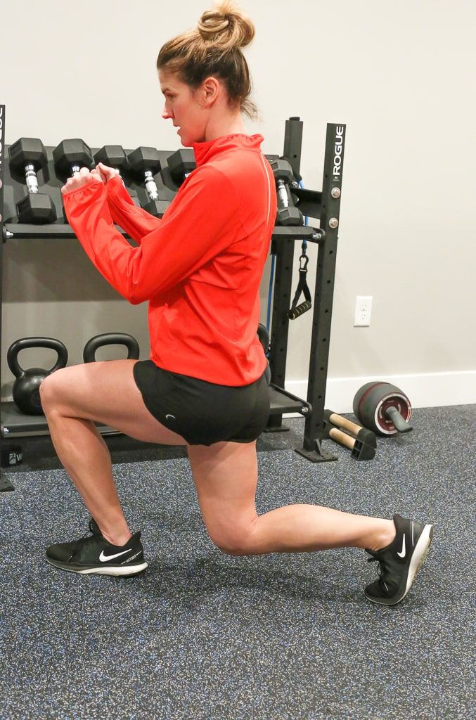 Maryea Flaherty in a red jacket and black shorts completing a reverse lunge exercise