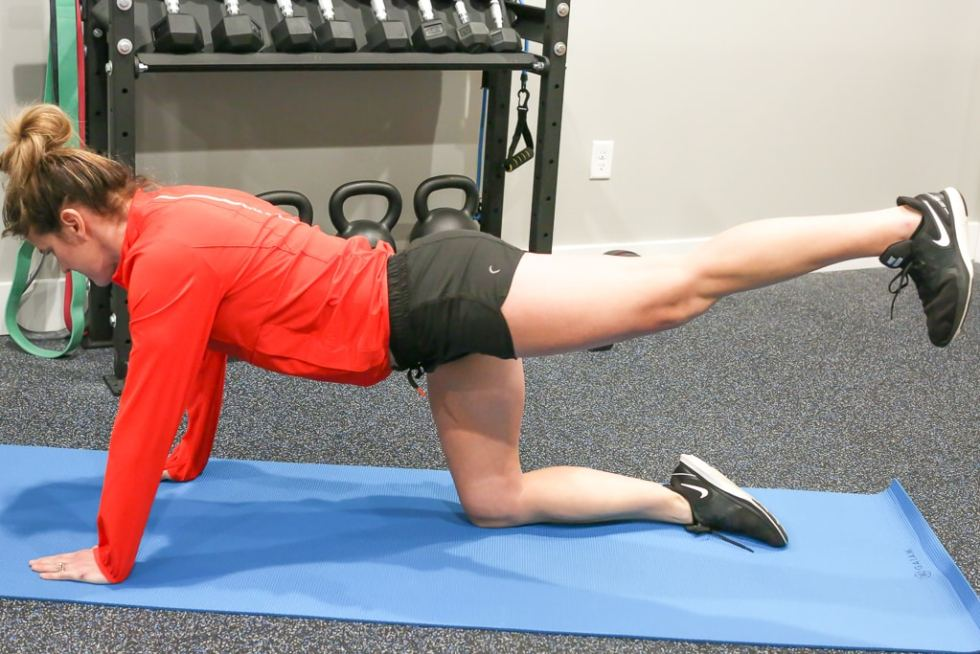 Maryea Flaherty in a red jacket and black shorts completing a donkey straight leg kick exercise