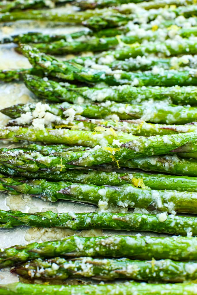 close up picture of baked asparagus that's been roasted with parmesan cheese and topped with lemon zest