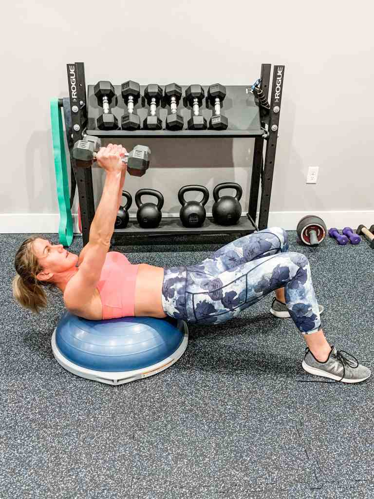 a woman in floral leggings and a sports bra laying on a bosu ball and arms over her head with dumbbells
