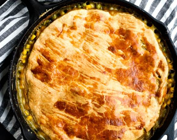 a vegetarian pot pie in a cast iron skillet with a striped napkin under the skillet