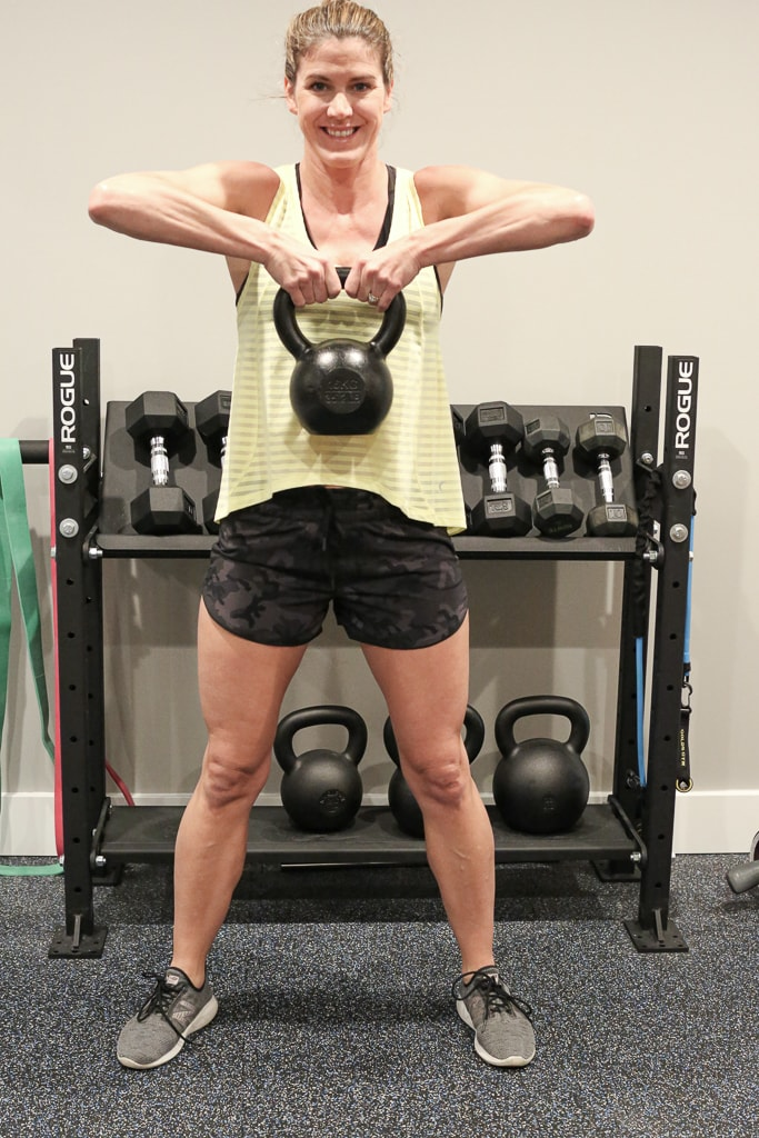 Woman in workout clothes holding a kettlebell for a full-body kettlebell workout