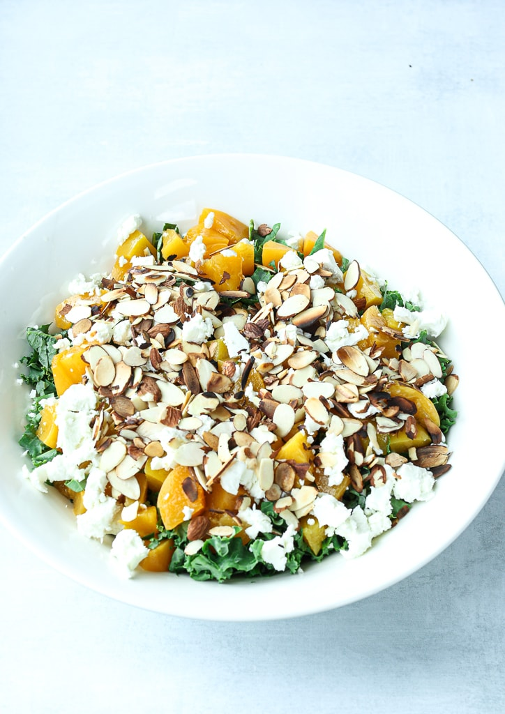 a white bowl with kale, peaches, goat cheese, and sliced almonds