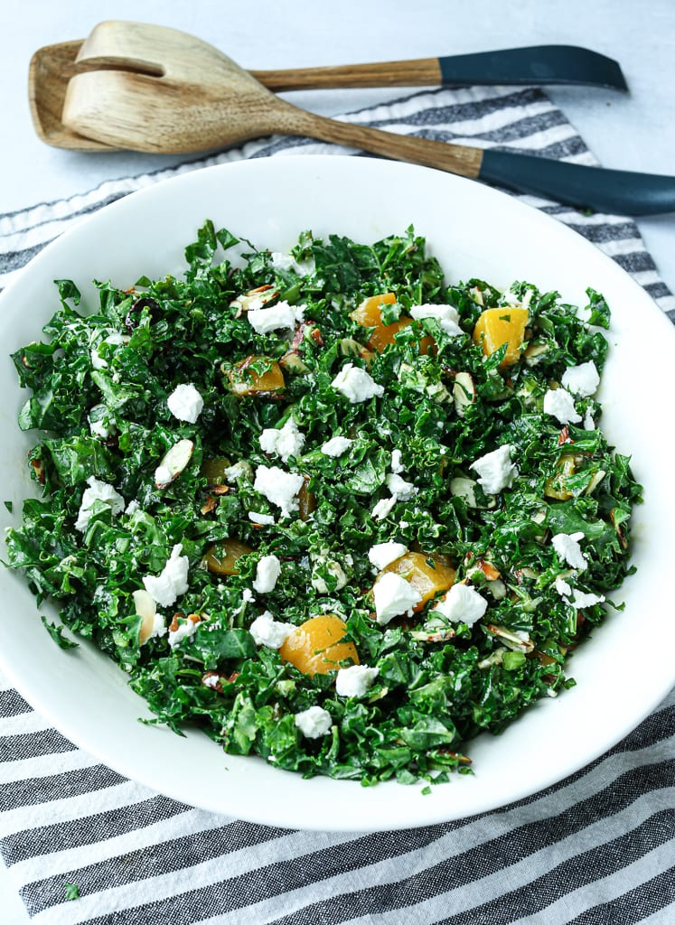 An overhead shot of the kale salad in a bowl with peaches and goat cheese and a striped napkin