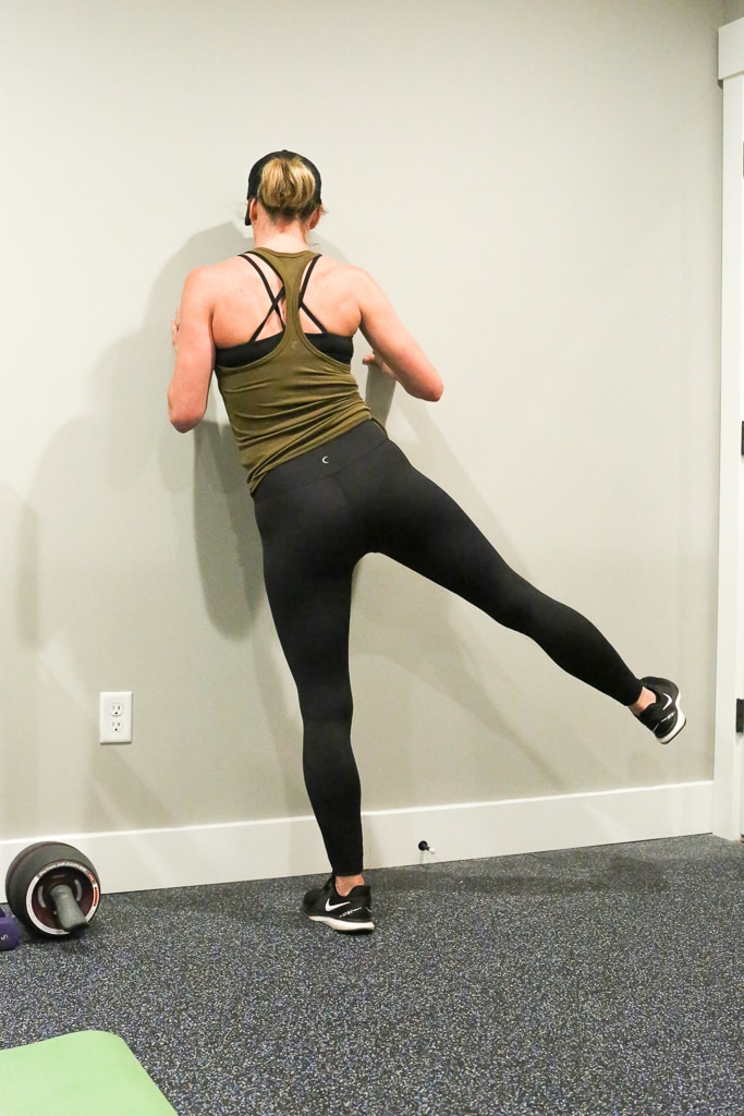 a woman against the wall completing leg lifts