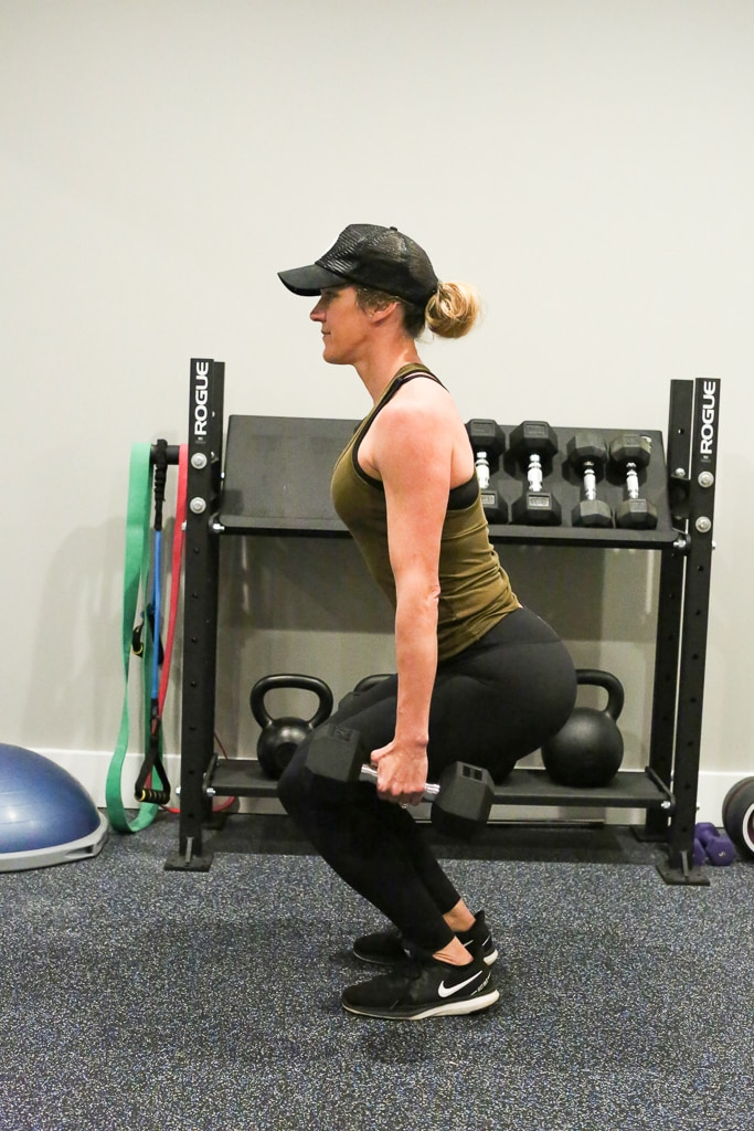 a woman doing a squat exercise with weights