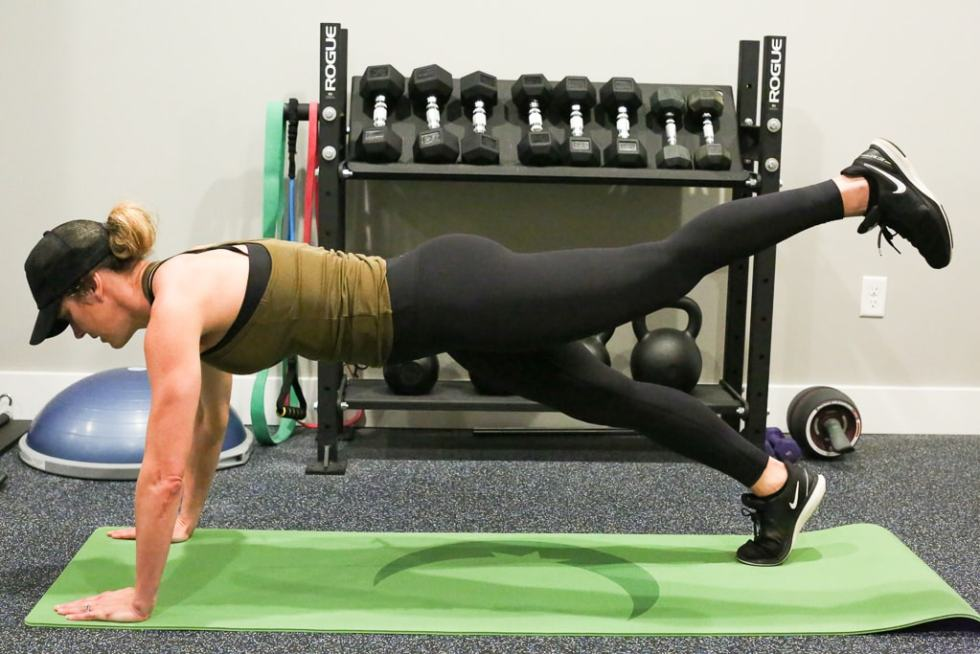 a woman performing high plank leg extension