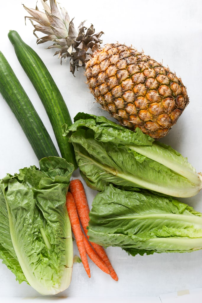 overhead shot of green juice ingredients--pineapple, 2 cucumbers, 3 hearts of romaine, 3 carrots, and a pineapple