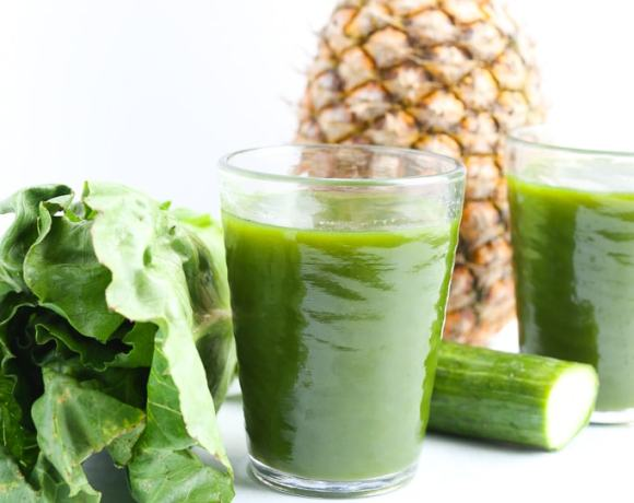 2 glasses of green juice with pineapple, romaine, and cucumber