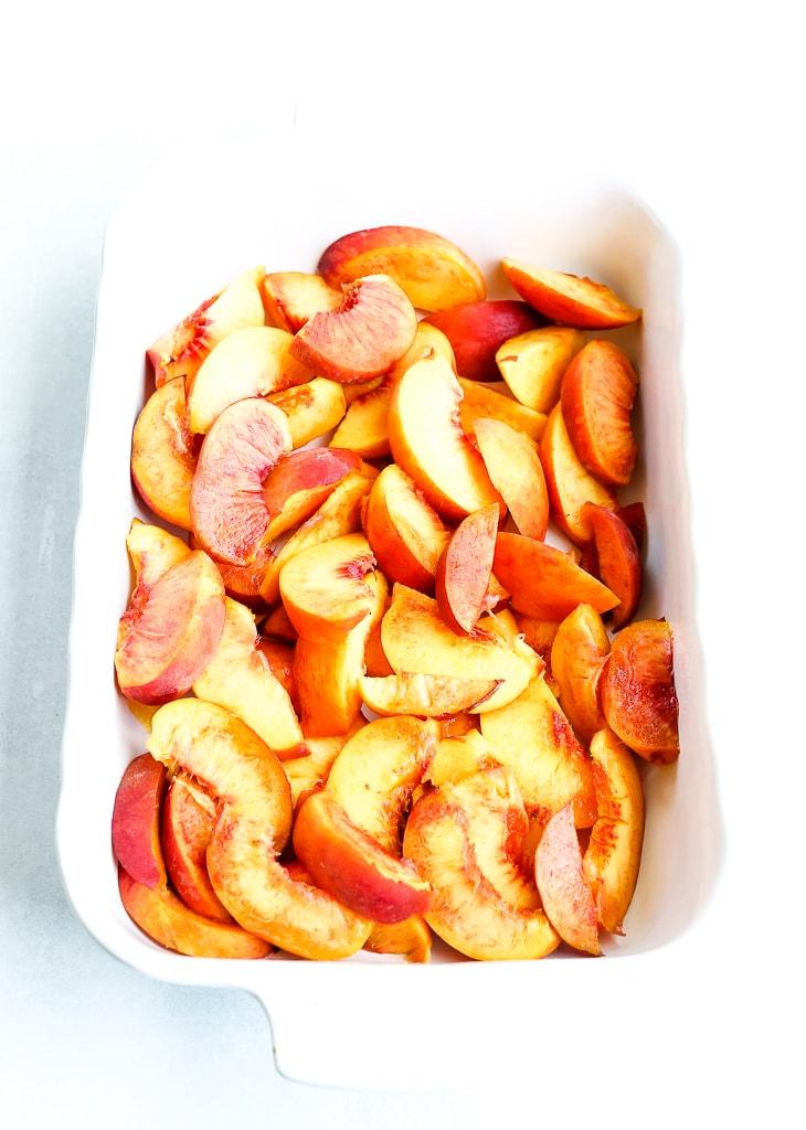 fresh sliced peaches in a white baking dish