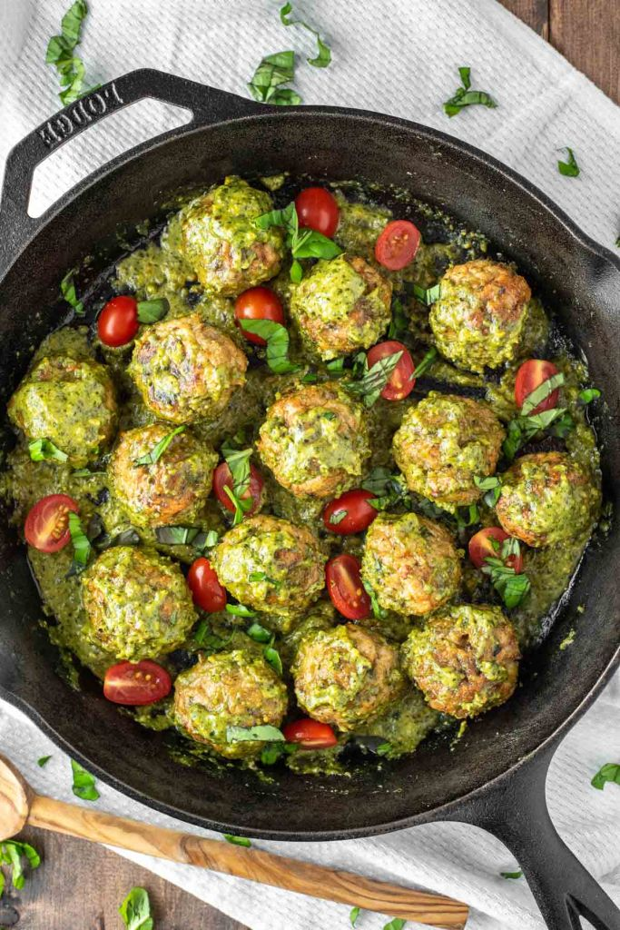 overhead shot of chicken meatballs in a pesto sauce in a black pan