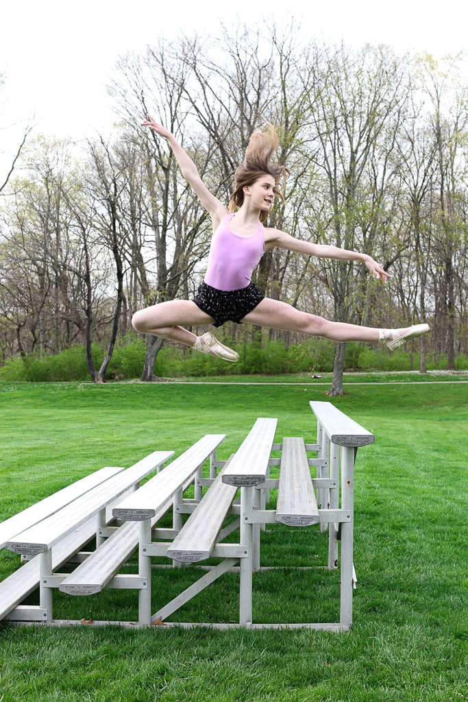 a girl in a flying leap in front of bleachers