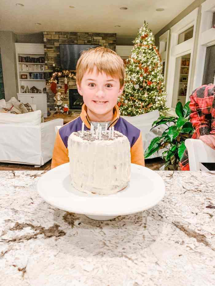 Luke with a big smile and birthday cake with candles in front on him