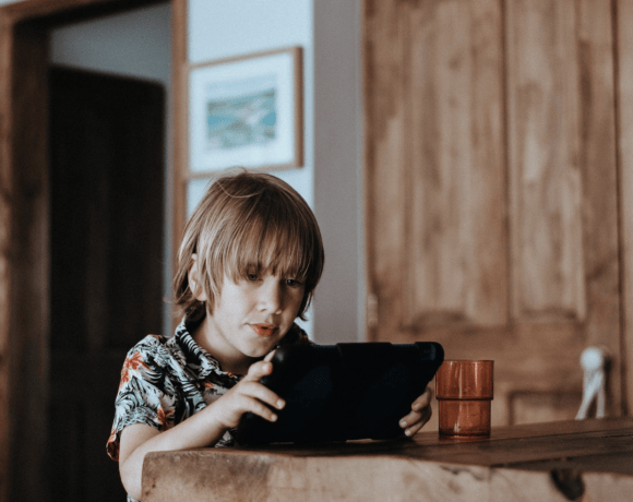 a young boy starting at an ipad screen, sitting at a wooden table