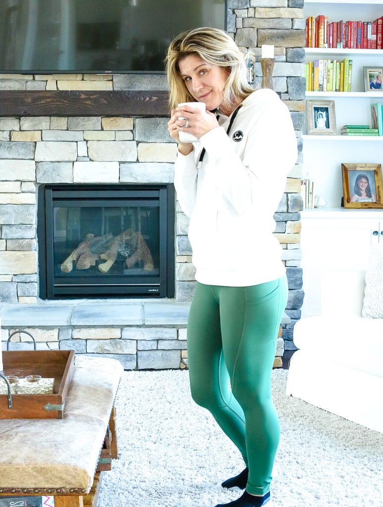 a woman standing with green leggings and a white hooding sipping from a cup of coffee