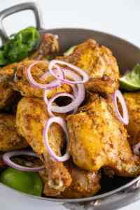 a pan ful of tandoori chicken with red onions