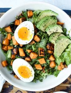 close up photo of breakfast salad with soft boiled egg, avocado and sweet potato