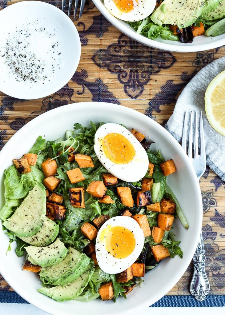 a plate of breakfast salad with fork and a lemon half