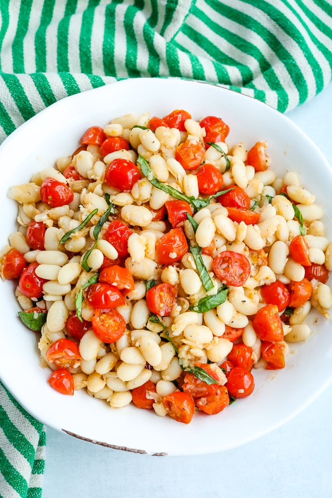 an overhead shot of White Beans with Tomatoes and Fresh Basil in a white bowl with a green and white striped napkin