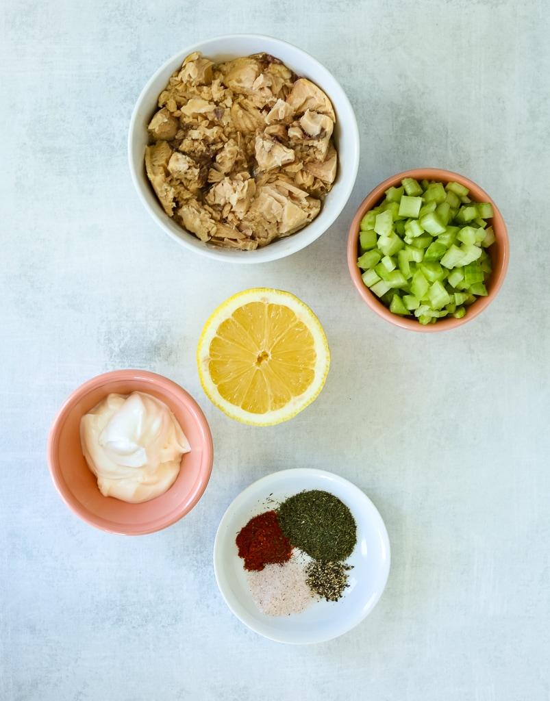 recipe ingredients overhead shot, cooked salmon chunks, chopped celery, mayo, Greek Yogurt, spices, half a lemon