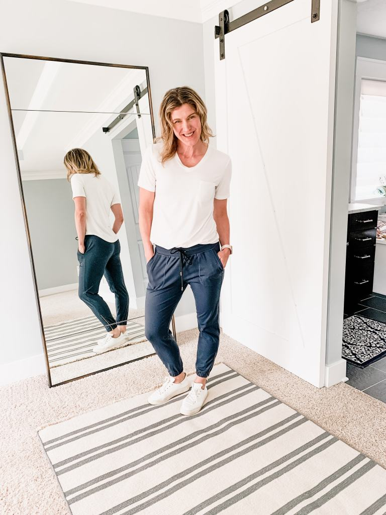 a woman in navy blue joggers and a white t shirt