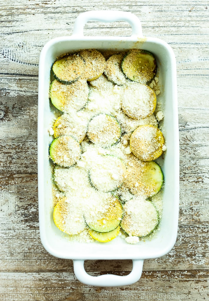 layers of zucchini, summer squash, parmesan cheese, and breadcrumbs in a white baking dish