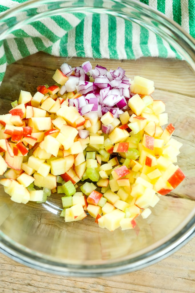 a glass bowl with chopped apples, celery, and red onion,