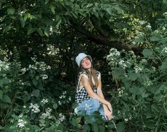 a young girl squatting by some flowers in the woods