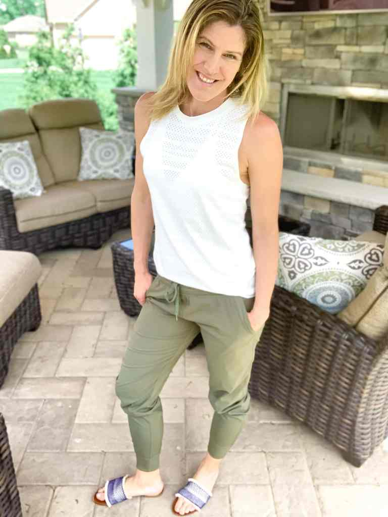 a woman in olive joggers and a white tank top on an outdoor patio