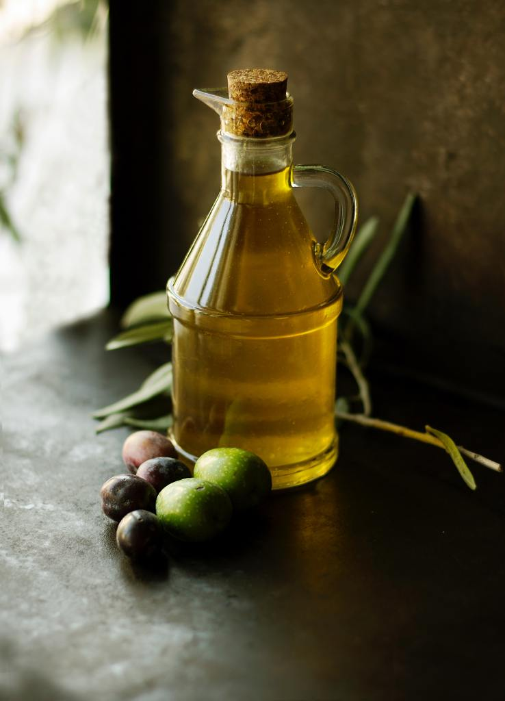 Bottle of Olive Oil with Olives Next To It