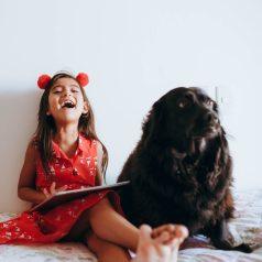 photo of girl sitting beside black dog