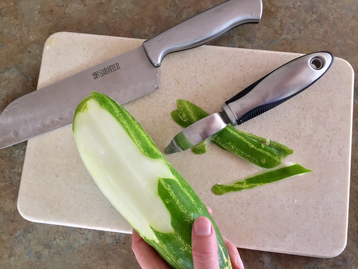 Cucumbers being peeled on a cutting board.