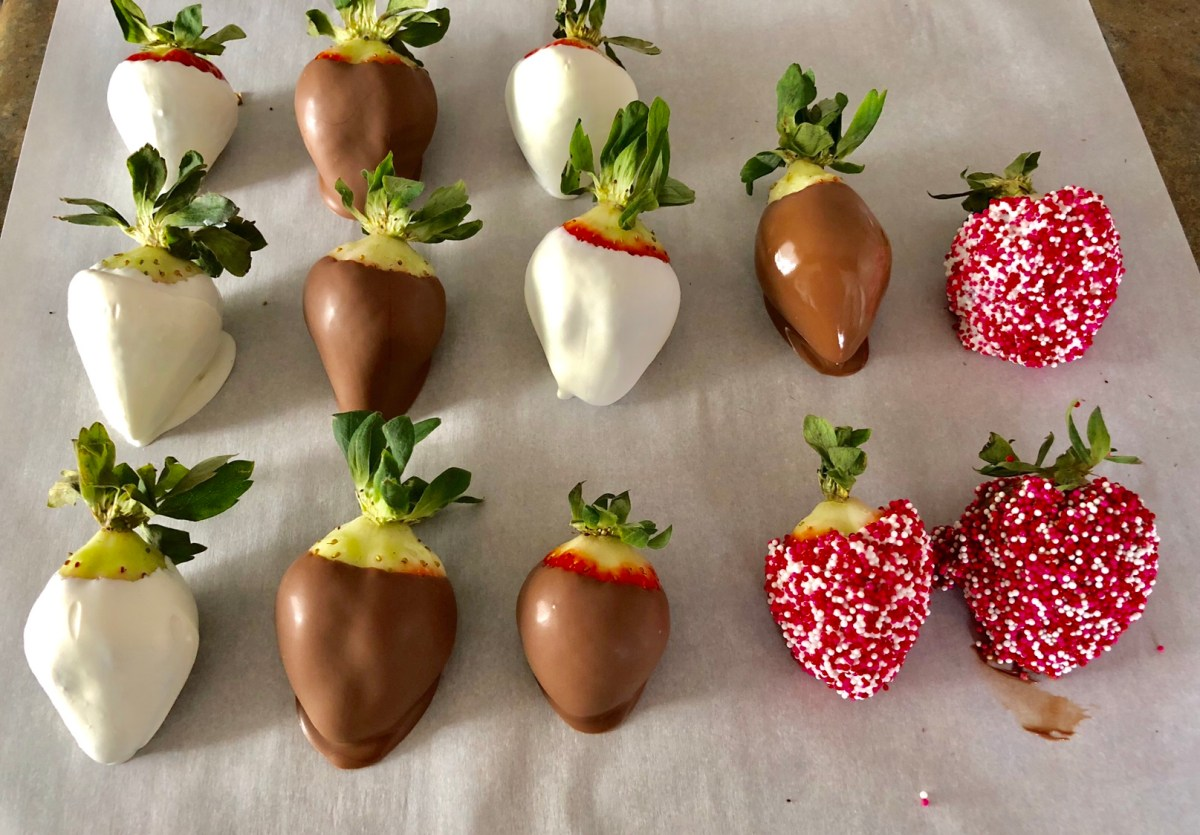 Chocolate dipped strawberries setting on wax paper.