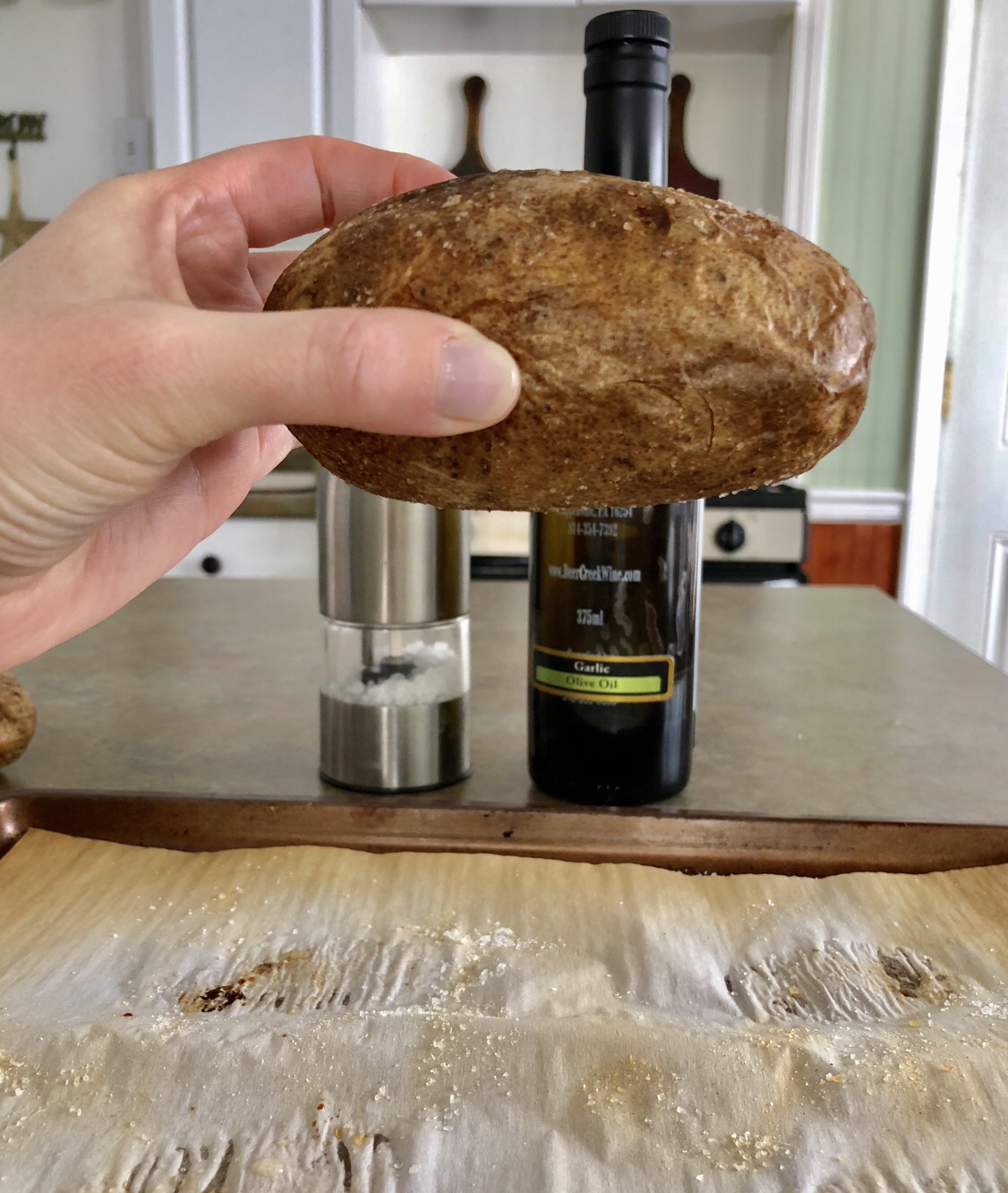 Baked potato held 6 inches over a baking sheet.