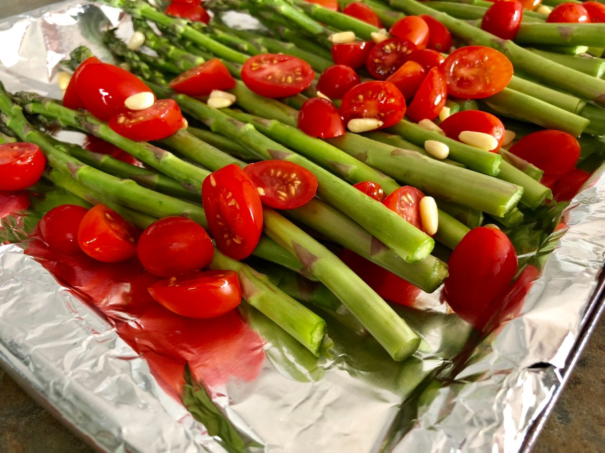 Trim the asparagus. Slice the tomatoes in half. Layer on a baking sheet sprayed with cooking spray. Top with pine nuts. #asparagus #roastedasparagus #sidedish #vegetablesidedish #springveggies