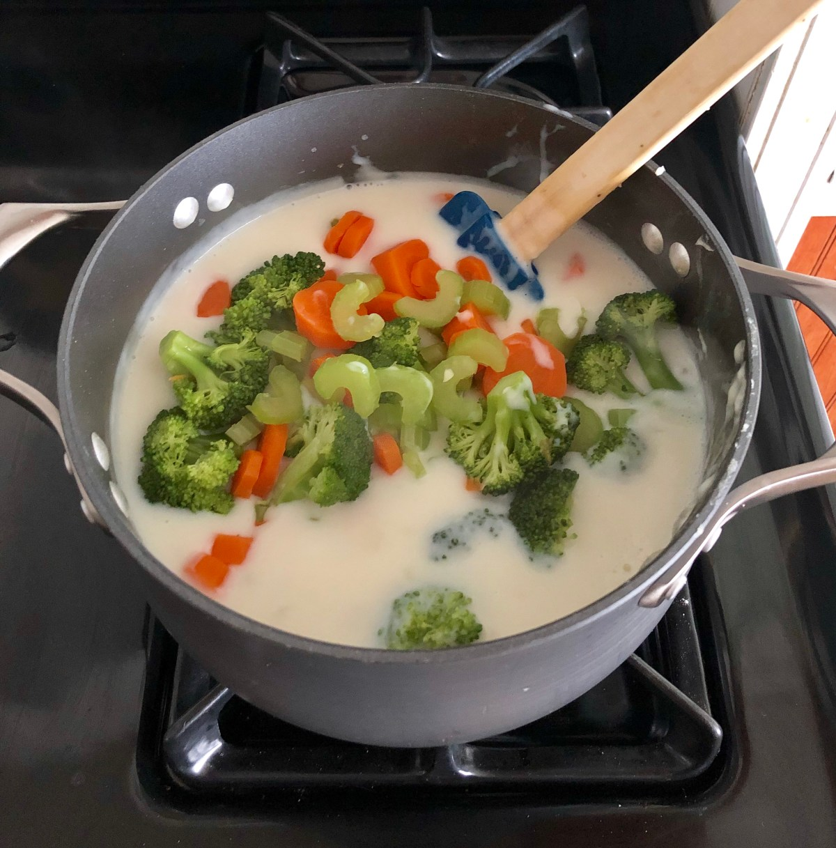 Broccoli, carrots, and celery are added back to the soup pot.