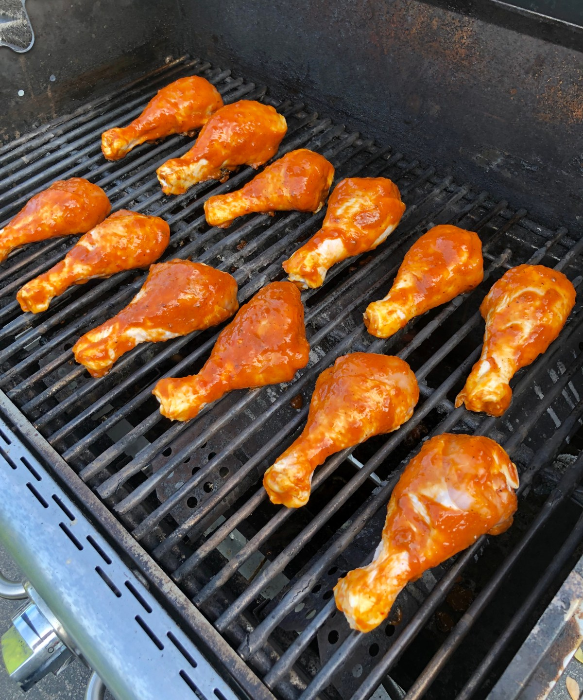 Chicken drumsticks covered in barbecue sauce on a grill rack.