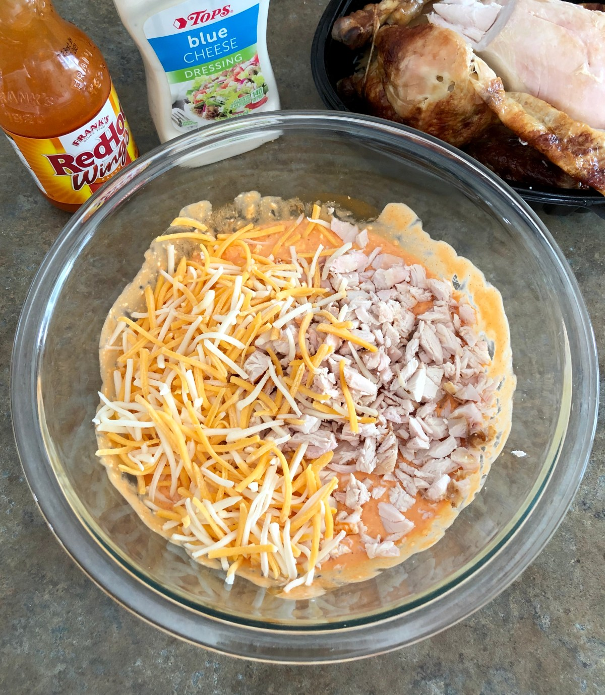 Cooked chicken and colby jack cheese are added to the bowl.