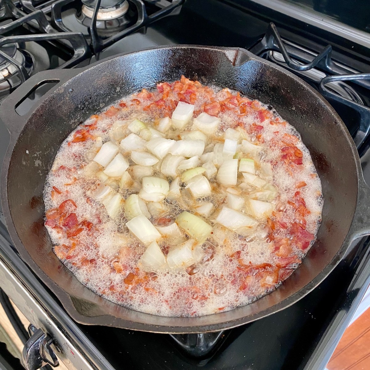 Chopped onions and bacon cooking in a cast iron skillet on a stovetop. #castironrecipes #breakfast #breakfastskillet #skilletrecipes #onepanrecipes #baconandeggs