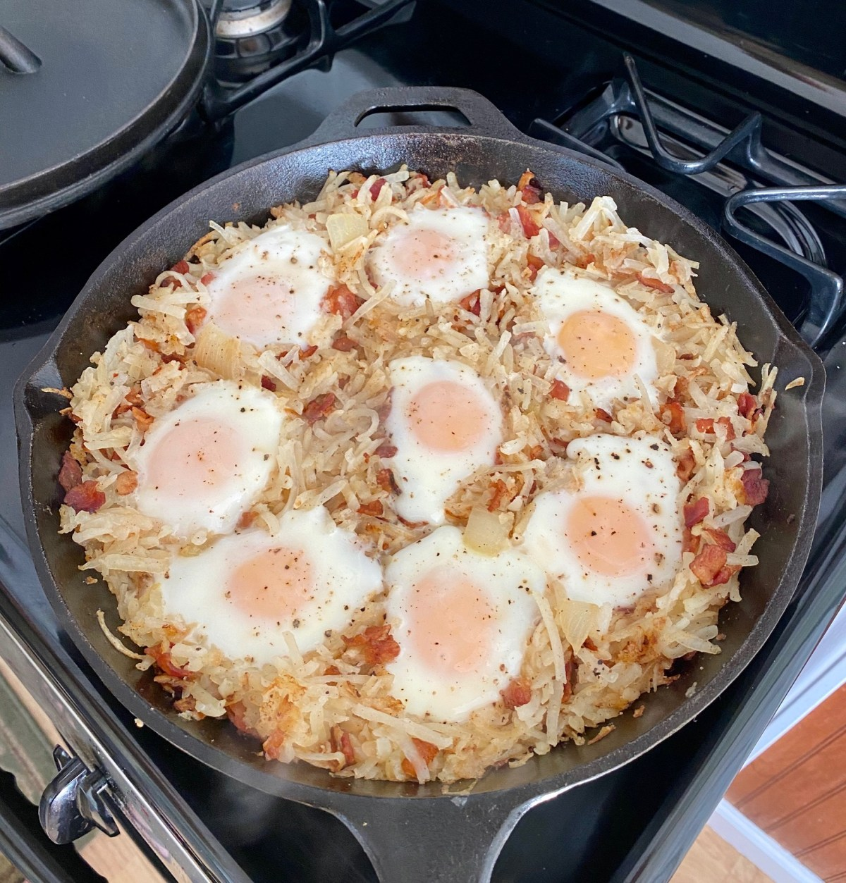 Eggs and hash browns cooking in a cast iron skillet on a stovetop. #castiron #breakfastideas #heartybreakfast #skilletbreakfast #brunchrecipes #hashbrownrecipes