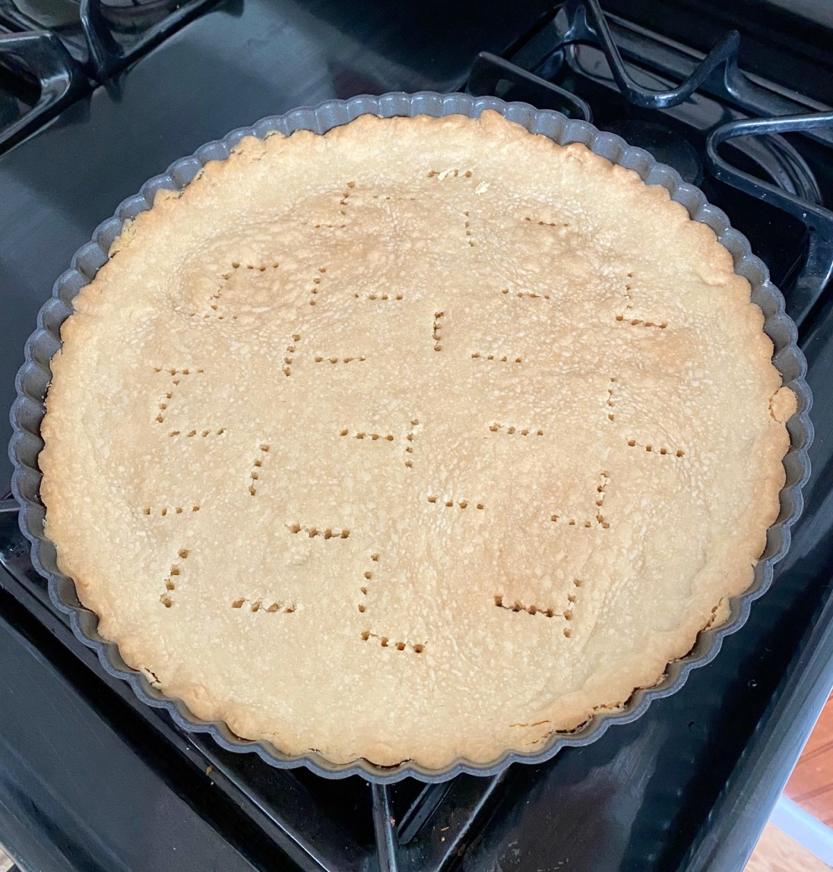 Tart crust baked in a tart pan cooling on the stovetop. #fruittart #whitechocolatedessert #dessert #fruitdessert #freshfruittart #brunchrecipes