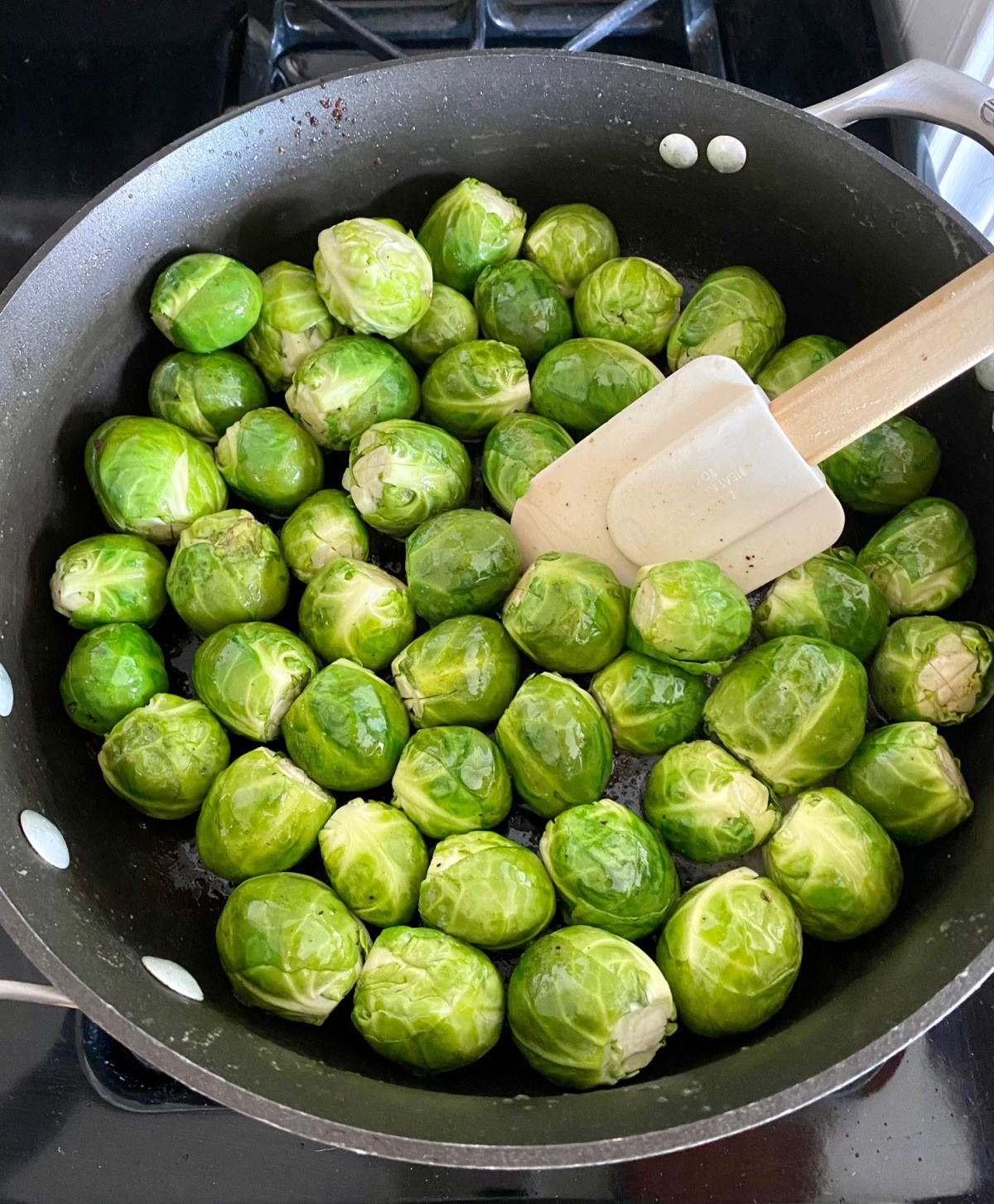 Brussels sprouts cooking in butter in a large skillet over medium heat. #maplebaconbrusselssprouts #brusselssprouts #holidaysidedish #dinnerrecipes #dinnerideas #healthyrecipes #healthydinnerrecipes