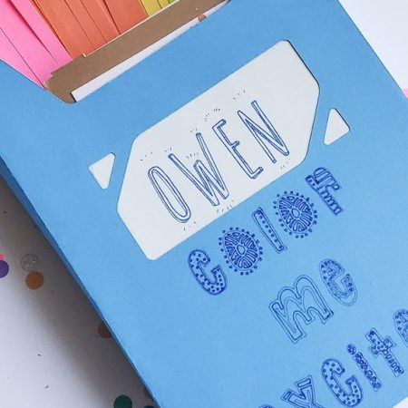 """Front image of blue crayon box envelope reads """"OWEN; color me excited"""". Rainbow tassels inside box, box laying on top of rainbow confetti."""