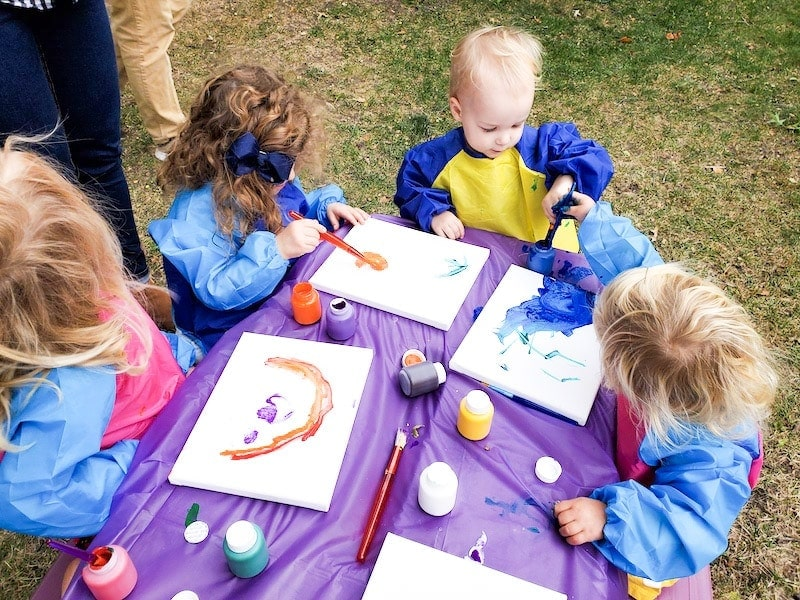 4 kids sitting at a small table with a purple tablecloth. Each child is painting a canvas