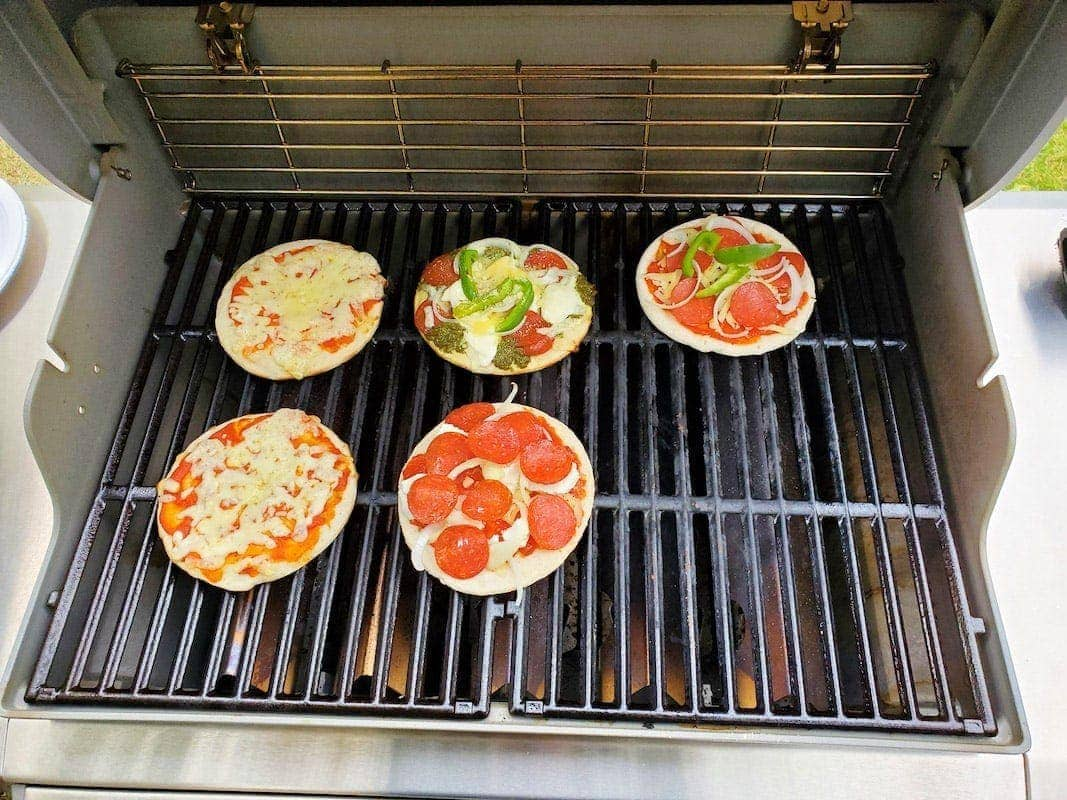 5 pizzas cooking on a grill